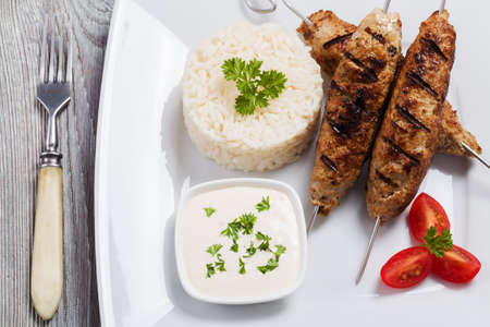 barbecued: Barbecued kofta - kebeb with rice and vegetables on a plate. Selective focus