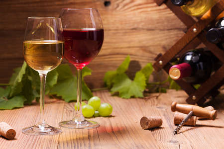 still life of wine: Glasses of red and white wine, served with grapes on a wooden background