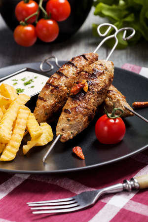 barbecued: Barbecued kofta - kebeb with fries and vegetables on a plate. Selective focus