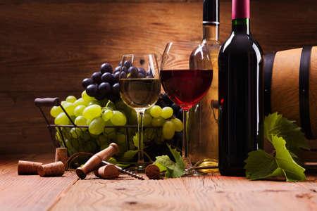赤と白ワインのグラスを添えて木製の背景のブドウ 写真素材