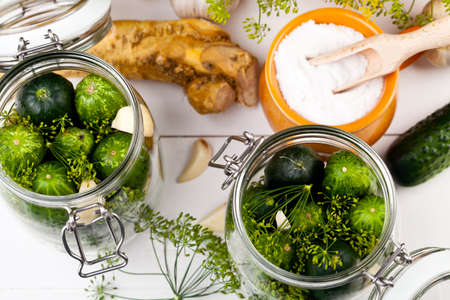 Homemade pickles in brine with garlic, dill and horseradish on wood board 版權商用圖片