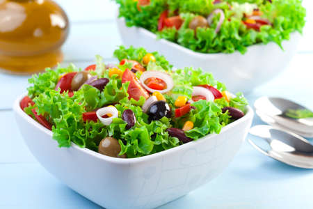 Fresh Mexican salad with olives and red beans on blue wood board