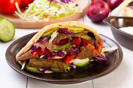 sandwich de pollo: Beef Kebab en un pan en tablero de madera