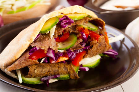 Beef Kebab in a bun on wood board