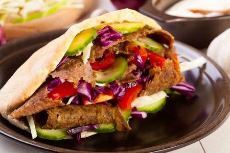 Beef Kebab in a bun on wood board