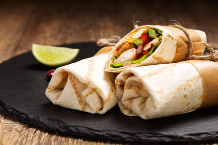 チキンと豆の木板に野菜でブリトーをラップします。 写真素材