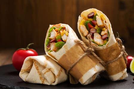 ensalada tomate: Burritos envuelve con pollo, frijoles y verduras en la tabla de madera