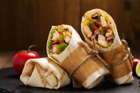 Burritos wraps with chicken, beans and vegetables on wood board Stock Photo