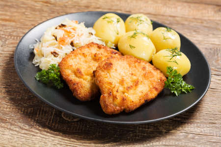 breaded pork chop: Fried pork chop in breadcrumbs, served with boiled potatoes and cabbage. Traditional Polish dish.