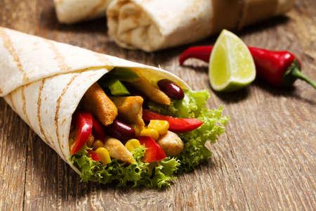 Burritos는 나무 널빤지에 닭고기, 콩 및 채소로 포장합니다.