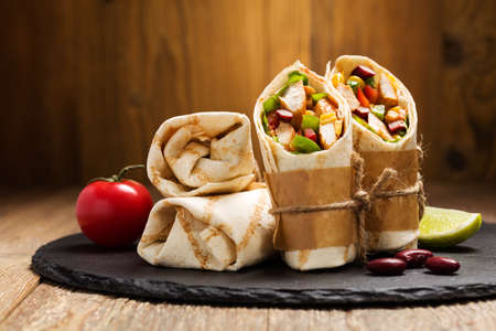 Burritos wraps with chicken, beans and vegetables on wood board Banco de Imagens