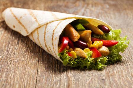 pollo: Burritos envuelve con pollo, frijoles y verduras en la tabla de madera