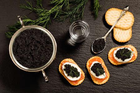 Caviar negro servido en galletas con vodka y aditivos Foto de archivo - 44784784