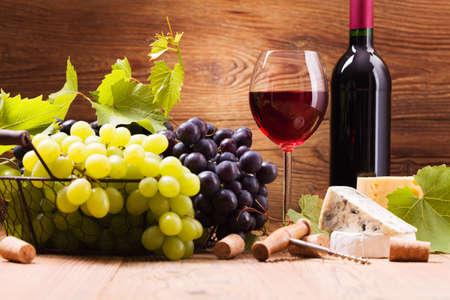 Glas rode wijn, geserveerd met druiven en kaas op een houten achtergrond
