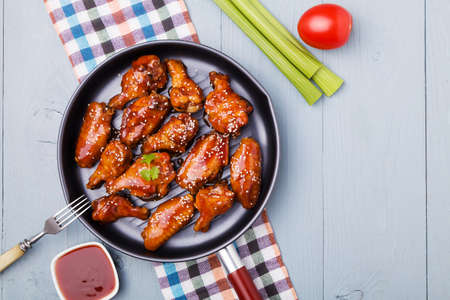 Baked chicken wings in honey sauce sprinkled with sesame seeds. Banco de Imagens