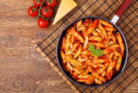 Penne with roasted chicken in tomato sauce on wooden table