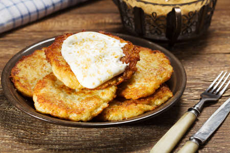 Homemade potato pancakes served with sour cream and brown sugar from cane on wooden board.