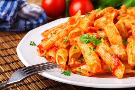 tomate: Penne with roasted chicken in tomato sauce on wooden table