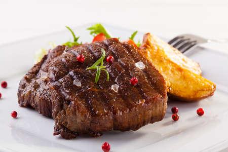 carne asada: Filete de ternera a la plancha con papas al horno y verduras en el plato