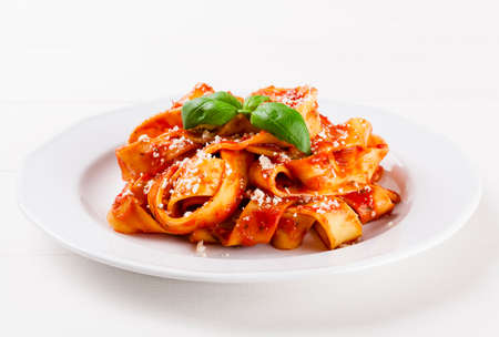 Pasta tagiatelle with tomato on white woodboard Standard-Bild