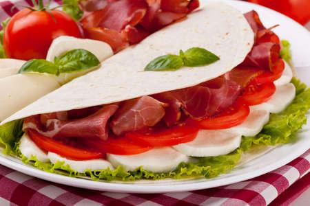 Italiaanse Piadina Romagnola met mozzarella, ham en groenten op witte woodboard Stockfoto
