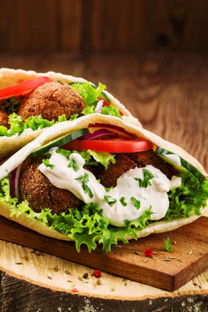 Falafel and fresh vegetables in pita bread on wooden table Stok Fotoğraf - 46295567
