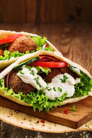 Falafel en verse groenten in pita brood op houten tafel