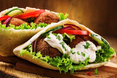 comida arabe: Falafel y verduras frescas en el pan de pita en mesa de madera Foto de archivo