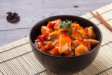 meat dish: Chinese chicken sweet and sour sauce, served with rice and vegetables on woodboard