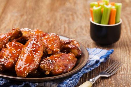 Ailes de poulet cuits dans la sauce au miel saupoudrés de graines de sésame. Banque d'images - 46276906