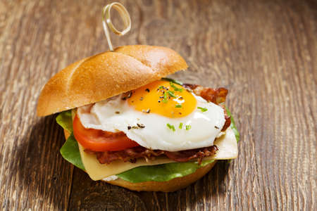 eggs and bacon: Sandwich with a fried egg, bacon, cheese and vegetables.