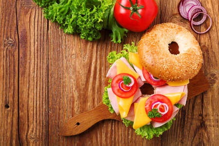 chicken sandwich: Healthy sandwich on a bagel with ham, cheese and vegetables. Top view.