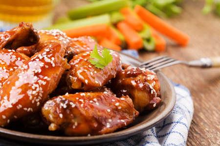 Gebakken kippenvleugeltjes in honing saus besprenkeld met sesamzaadjes. Stockfoto - 46277095