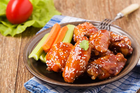 Baked chicken wings in honey sauce sprinkled with sesame seeds. Foto de archivo