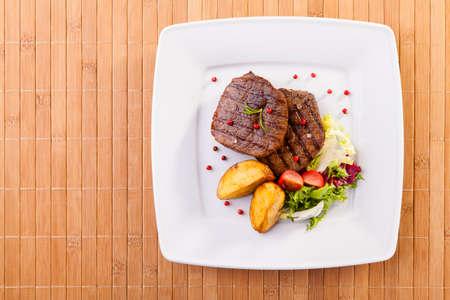 접시에 구운 감자와 야채와 구운 쇠고기 스테이크
