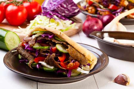 dinner plate: Beef Kebab in a bun on woodboard