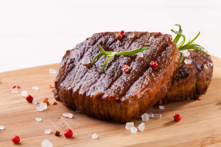 Grilled beef steak on wooden board