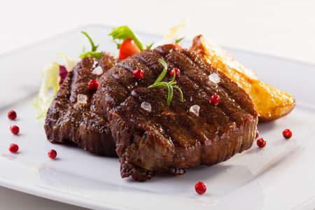grilled potato: Grilled beef steak with baked potatoes and vegetables on plate Stock Photo