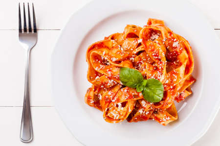 spaghetti dinner: Pasta tagiatelle with tomato on white woodboard Stock Photo