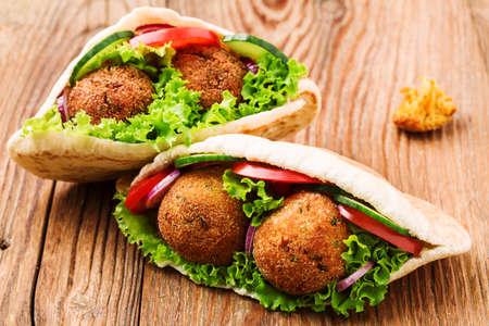 Falafel and fresh vegetables in pita bread on wooden table Banco de Imagens - 47944538