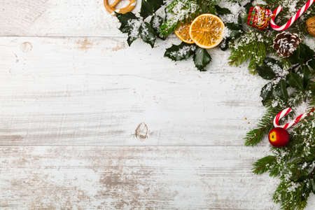 bordes decorativos: Christmas decoration with dried oranges, spruce, holly, snow, against the backdrop of the old white boards. Foto de archivo