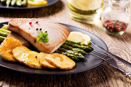 lemon: Grilled tuna steak served on asparagus with roasted zmieniakami on a black plate.