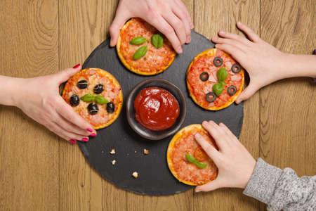 mini pizza: The family treats a mini pizza.