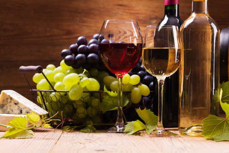 Glasses of red and white wine, served with grapes and cheese on a wooden background