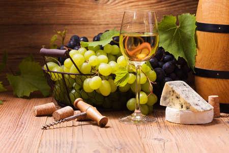 Glas Weißwein, serviert mit Trauben und Käse auf einem hölzernen Hintergrund