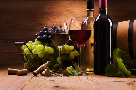 Bicchieri di vino rosso e bianco, servito con uva su sfondo di legno Archivio Fotografico