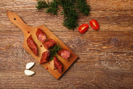 Delicious smoked sausage, sliced on a wooden board with spices.