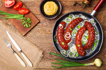 chorizos asados: salchichas fritas en una sartén con cebollas. Foto de archivo
