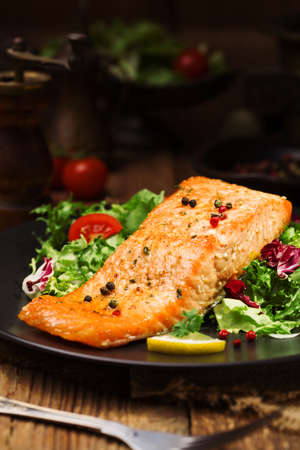 plates of food: Baked salmon served with fresh vegetables.