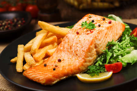 fish: Baked salmon served with french fries and fresh vegetables.